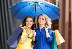 Schönes blondes und Brunette mit blauem Regenschirm Lizenzfreies Stockbild