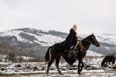 Schönes blondes Viking in einem schwarzen Kap zu Pferd Stockbild
