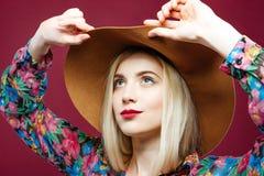 Schönes blondes vorbildliches Wearing Fashionable Hat und buntes Hemd wirft auf rosa Hintergrund im Studio auf Stockbilder