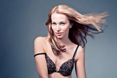 Schönes blondes weibliches Modell auf blauem Hintergrund Lizenzfreie Stockfotografie