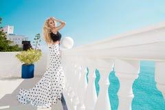 Schönes blondes weibliches Modell, das nahe bei einem exklusiven Pool in einem langen Hochzeitskleid steht Stockfotografie