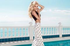 Schönes blondes weibliches Modell, das nahe bei einem exklusiven Pool in einem langen Hochzeitskleid steht Stockbilder
