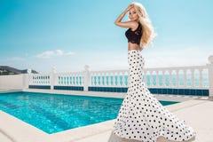 Schönes blondes weibliches Modell, das nahe bei einem exklusiven Pool in einem langen Hochzeitskleid steht Lizenzfreies Stockfoto