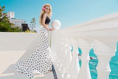 Schönes blondes weibliches Modell, das nahe bei einem exklusiven Pool in einem langen Hochzeitskleid steht Stockfotos