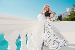 Schönes blondes weibliches Modell, das nahe bei einem exklusiven Pool in einem langen Hochzeitskleid steht Lizenzfreie Stockfotografie