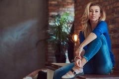 Schönes blondes weibliches Sitzen auf einer Tabelle gegen eine Backsteinmauer in einem Studio mit einem Dachbodeninnenraum Stockbild