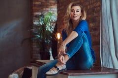 Schönes blondes weibliches Sitzen auf einer Tabelle gegen eine Backsteinmauer in einem Studio mit einem Dachbodeninnenraum Lizenzfreie Stockbilder