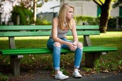 Schönes blondes woamn steht auf einer Bank im Park still Stockfoto