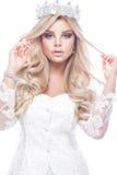 Schönes blondie Mädchenmodell im Spitzehochzeitskleid mit Locken und in der Krone auf ihrem Kopf Schönes lächelndes Mädchen lizenzfreie stockbilder