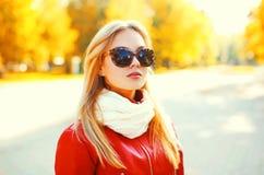 Schönes Blondinetragen Sonnenbrille und rote Jacke mit Schal im Herbst Lizenzfreie Stockfotos