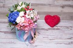 Schönes Blumengesteck im Hutkasten mit Action-Figur-Herzen, schäbiger weißer Holztisch Lizenzfreie Stockbilder