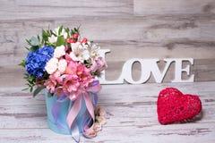 Schönes Blumengesteck im Hutkasten mit dem Aufschriftliebes- und -Action-Figur-Herzen, schäbiger weißer Holztisch Stockfotos