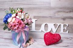 Schönes Blumengesteck im Hutkasten mit dem Aufschriftliebes- und -Action-Figur-Herzen, schäbiger weißer Holztisch Lizenzfreie Stockfotos