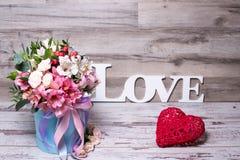 Schönes Blumengesteck im Hutkasten mit dem Aufschriftliebes- und -Action-Figur-Herzen, schäbiger weißer Holztisch Stockbilder