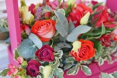 Schönes Blumengesteck von Roten, Rosa- und Burgunder-Blumen in einer rosa Holzkiste stockfoto