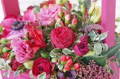 Schönes Blumengesteck von Roten, Rosa- und Burgunder-Blumen in einer rosa Holzkiste stockbild