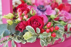 Schönes Blumengesteck von Roten, Rosa- und Burgunder-Blumen in einer rosa Holzkiste stockfotografie