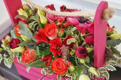 Schönes Blumengesteck von Roten, Rosa- und Burgunder-Blumen in einer rosa Holzkiste lizenzfreie stockfotos