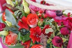 Schönes Blumengesteck von Roten, Rosa- und Burgunder-Blumen in einer rosa Holzkiste lizenzfreie stockbilder