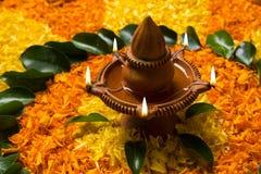 Schönes Blumenrangoli oder -dekoration mit Lehmlampe für diwali oder irgendein indisches Festival Stockbilder