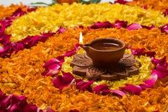 Schönes Blumenrangoli oder -dekoration mit Lehmlampe für diwali oder irgendein indisches Festival Lizenzfreie Stockbilder