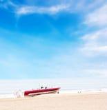 Schönes Boot auf Strand unter blauem Himmel und Wolken Stockbilder