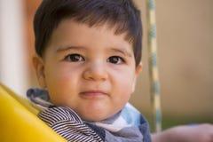 Schönes brasilianisches Baby, das Kamera betrachtet Baby auf dem swin stockbilder