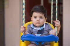 Schönes brasilianisches Baby, das Kamera betrachtet Baby auf dem swin stockfoto