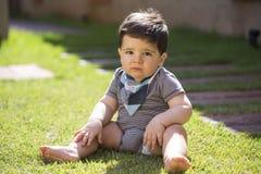 Schönes brasilianisches Baby im Gras, das Kamera betrachtet Ser lizenzfreies stockbild