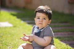Schönes brasilianisches Baby im Gras, das Kamera betrachtet Ser stockfotos