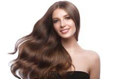Schönes braunhaariges Mädchen in der Bewegung mit einem tadellos Lockenhaar und klassisches Make-up Schönes lächelndes Mädchen lizenzfreie stockfotos