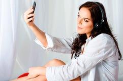 Schönes braunhaariges Mädchen in einem weißen Hemd- und Hosenensitzen lizenzfreie stockfotografie