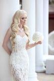 Schönes Braut-Porträt, das den Hochzeitsblumenstrauß aufwirft in der Spitze hält stockfotografie