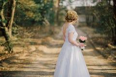 Schönes Brautfrauenporträt mit dem Brautblumenstrauß, der in ihrem Hochzeitstag aufwirft Lizenzfreies Stockfoto
