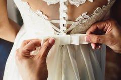 Schönes Brautkleid Zeugen Sie die Bindung eines Bogenhochzeitskleides auf der Braut stockbild