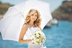 Schönes Brautmädchen im Hochzeitskleid mit weißem Regenschirm und BO Lizenzfreies Stockfoto