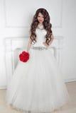 Schönes Brautmädchen mit dem Blumenstrauß der roten Rosen, der in modernem int aufwirft Stockbilder