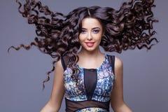 Schönes Brunette-Mädchen mit dem gesunden langen Haar Stockfoto
