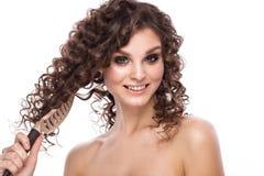 Schönes brunette Mädchen mit einem tadellos gelockten Haar mit einer Haarbürste und klassisches Make-up Schönes lächelndes Mädche stockfoto