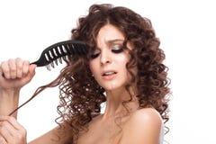 Schönes brunette Mädchen mit einem tadellos gelockten Haar mit einer Haarbürste und klassisches Make-up Schönes lächelndes Mädche lizenzfreie stockbilder