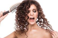 Schönes brunette Mädchen mit einem tadellos gelockten Haar mit einer Haarbürste und klassisches Make-up Schönes lächelndes Mädche stockfotografie