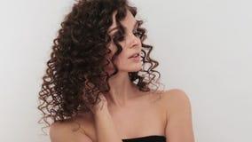 Schönes brunette Mädchen mit einem tadellos gelockten Haar und klassisches Make-up, das im Studio aufwirft Schönes lächelndes Mäd stock video