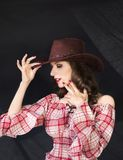 Schönes Brunettecowgirl im Cowboyhut auf dunklem Hintergrund Lizenzfreie Stockbilder