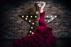 Schönes Brunettefrauenmodell im roten Luxuskleid lizenzfreie stockfotos