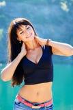 Schönes Brunettemädchen, das auf der Küste im Berg steht lizenzfreie stockfotografie