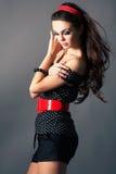 Schönes Brunettemädchen, das auf dunklem Hintergrund aufwirft stockfotos