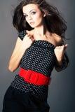 Schönes Brunettemädchen, das auf dunklem Hintergrund aufwirft lizenzfreie stockbilder
