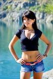 Schönes Brunettemädchen, das auf einer Hochlandküste steht Lizenzfreie Stockfotos