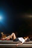 Schönes Brunettemädchen, das auf Fliesen legt Stockfotografie