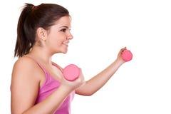 Schönes Brunettemädchen, das ein rosafarbenes Gewicht anhält Lizenzfreie Stockfotos